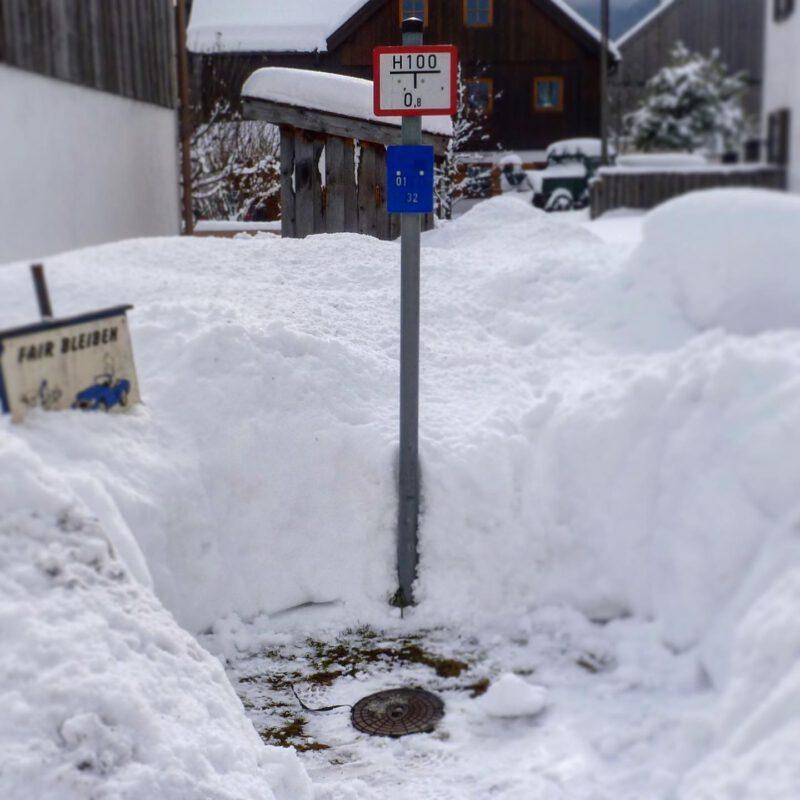 Unterflurhydrant mit Hydrantenschild im Schnee