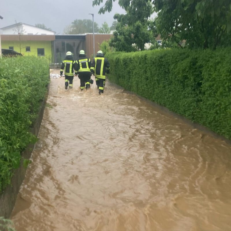 Feuerwehrleute waten auf einem überfluteten Fußweg zwischen Wohnhäusern in der Wertinger Industriestraße. Im Hintergrund der im Bau befindliche neue städtische Kindergarten.