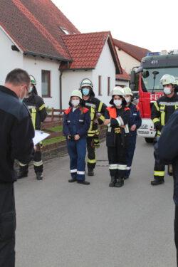 Die Löschgruppe steht vor dem Feuerwehrauto, im Vordergrund ist einer der Schiedsrichter zu sehen.