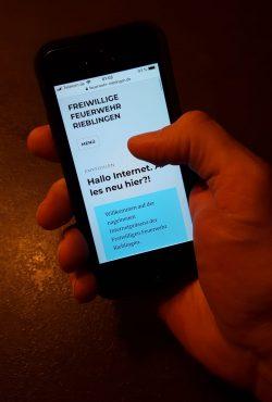 Bild eines Mobiltelefons, auf dem die Website der Feuerwehr Rieblingen angezeigt wird.