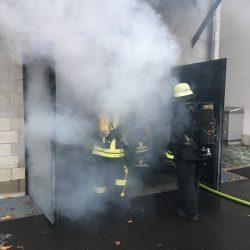 Feuerwehrleute stehen im Rauch vor einer geöffneten Garage des Brandhauses in der Staatlichen Feuerwehrschule Würzburg.
